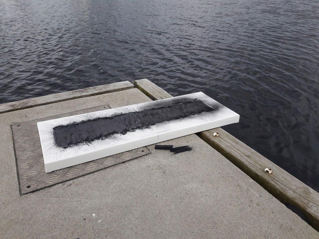 Ein Leinwandbildliegt auf der Hafenmauer und ragt darüber hinaus